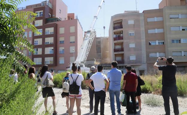 Gente mirando como derrumban un edificio