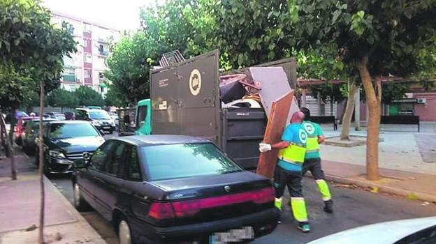 Operarios de los servicios municipales recogiendo enseres de la vía pública